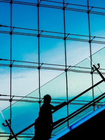 Silhouette of a man going up escalators, with blue sky out the window photo