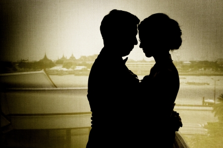 teen love: silhouette of couple holding with Thai background