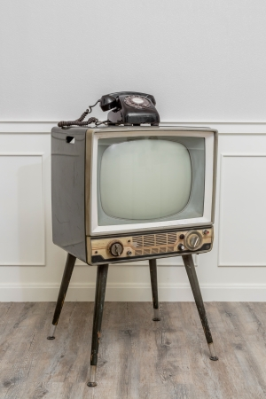 Old Television with 4 legs in the corner of vintage room and a black old telephone on it photo