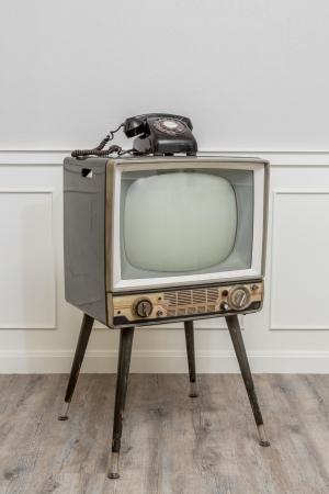 Oude televisie met 4 benen in de hoek van vintage kamer en een zwarte oude telefoon op het