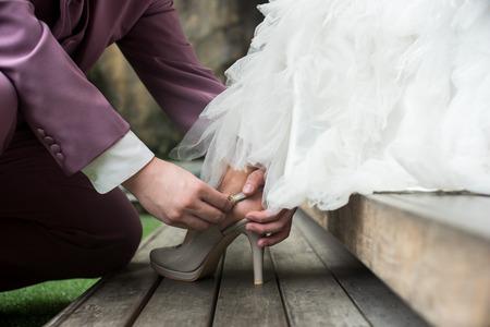 부드러운 빈티지 톤 이미지 신랑 신부 그녀의 신발에 퍼 팅을 돕는 스톡 콘텐츠