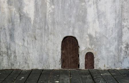 wooden small door and bigger door on concrete grungy wall with wooden floor photo