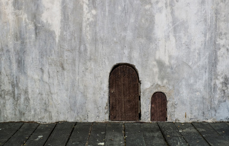 bigger: wooden small door and bigger door on concrete grungy wall with wooden floor Stock Photo