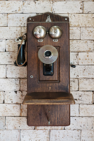 old telephone hanging on brick wall
