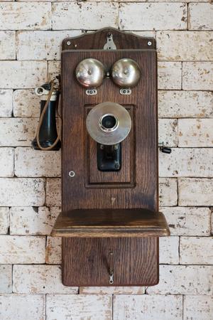 cabina telefonica: vieja colgando de teléfono en la pared de ladrillo