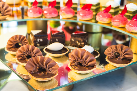 Different sort of beautiful pastry, small colorful sweet cakes Standard-Bild