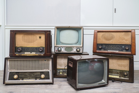oldie things. radios, tvs, camera, and frame on wooden floor Banque d'images