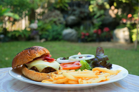eating breakfast: Cheese beef burger in the park Stock Photo
