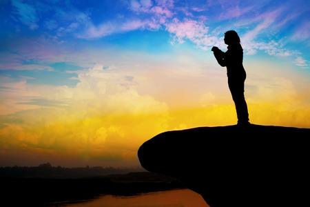 alabando a dios: Silueta de niña rezando en la colina Foto de archivo