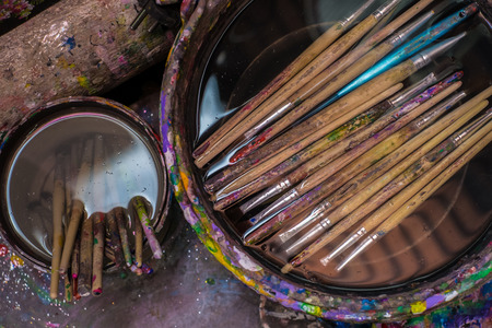 utilized: many paint brushes in water after used Stock Photo