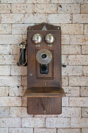 telefono antico: vecchio telefono appeso sul muro di mattoni Archivio Fotografico