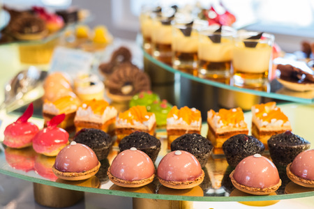 Different sort of beautiful pastry, small colorful sweet cakes Archivio Fotografico