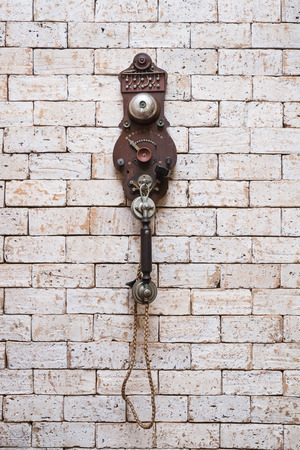 old telephone hanging on brick wall photo