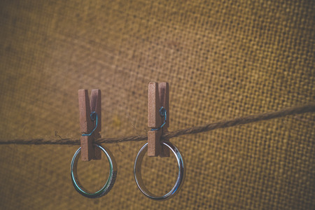 couple rings hanging with wooden paper clip on rope with old fabric background photo