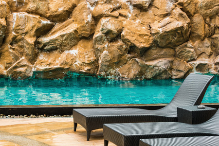 seat by the swimming pool with stone background photo