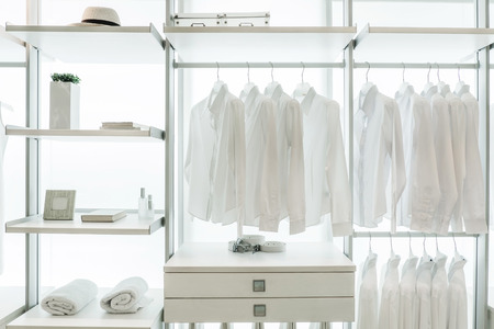 white shirts hanging on white built-in cloths racks, with drawers and other accessories Standard-Bild