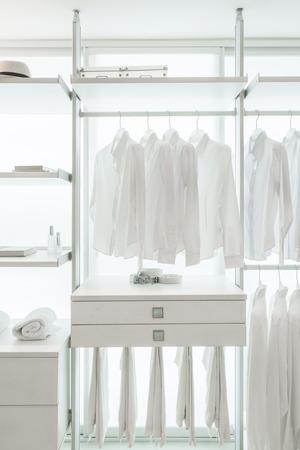 weiße T-Shirts hängen auf weißem eingebauten Tücher Racks, mit Schubladen und anderes Zubehör
