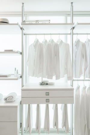 laundry hanger: white shirts hanging on white built-in cloths racks, with drawers and other accessories Stock Photo