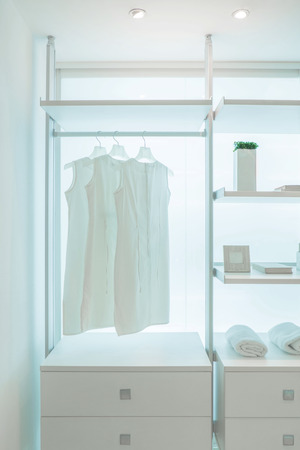 white shirts hanging on white built-in cloths racks, with drawers and other accessories photo