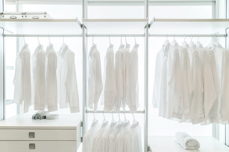 white shirts hanging on white built-in cloths racks, with drawers and other accessories Foto de archivo