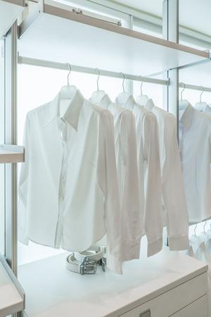 Weiße T-Shirts hängen auf weißem eingebauten Tücher Racks, mit Schubladen und anderes Zubehör Standard-Bild - 31062593
