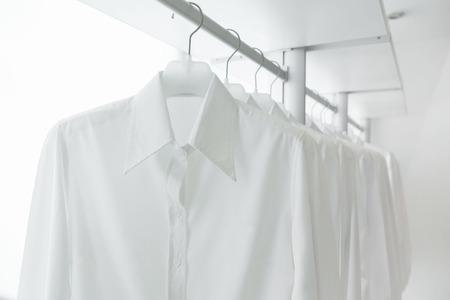 Camicie bianche appese su bianco built-in panni rack, con cassetti e altri accessori Archivio Fotografico - 31062595
