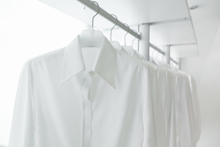 white shirts hanging on white built-in cloths racks, with drawers and other accessories Фото со стока