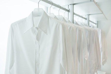 laundry room: white shirts hanging on white built-in cloths racks, with drawers and other accessories Stock Photo