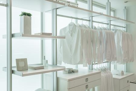 서랍 및 기타 액세서리와 함께 흰색 내장 옷걸이에 매달려있는 흰색 셔츠 스톡 콘텐츠