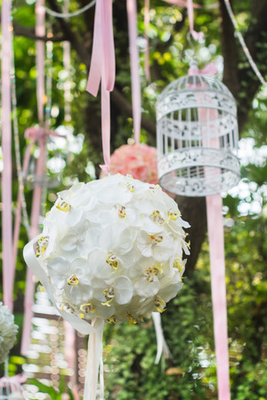 bouquet hanging from the tree with birdcage. Decoration in the wedding party