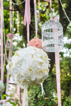 Bouquet von dem Baum mit Vogelkäfig hängt. Dekoration in der Hochzeitsgesellschaft