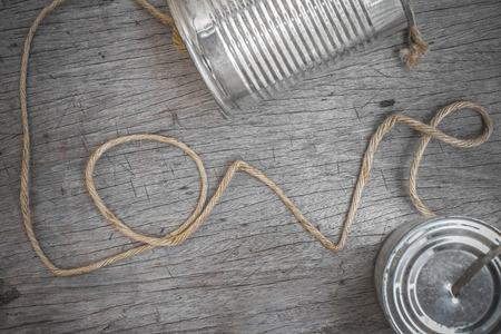 Latas de teléfono con la cuerda de conexión en forma de la palabra amor sobre fondo de madera Foto de archivo - 31062641