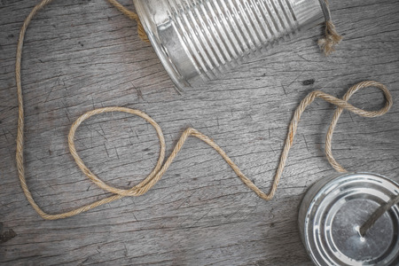 tins telephone with rope connecting shaped the word love on wooden background photo