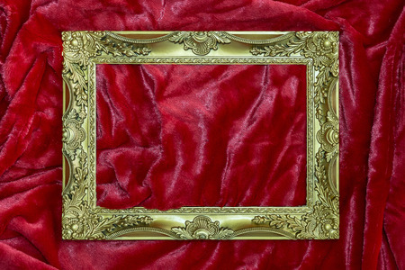 golden frame on red wrinkled fabric photo