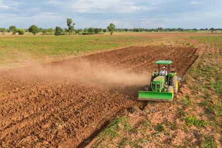 agriculture machinery: Thai farmer plowing the soil on his tractor
