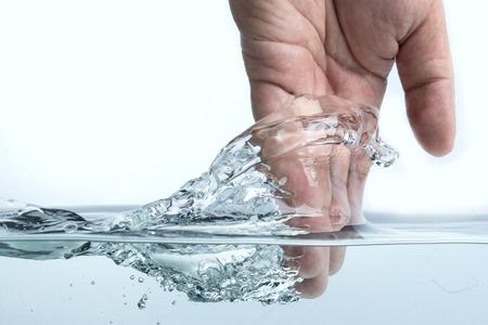 puros: tocar la superficie del agua de la mano, aislados en fondo blanco Foto de archivo