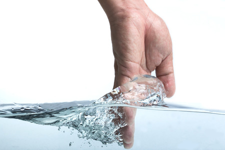 hand water: hand touching the surface of water, isolated on white background Stock Photo
