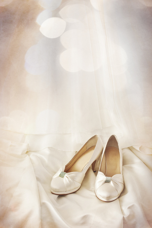 brides shoes on wedding bridal dress with bokeh foreground and layered with grungy texture photo
