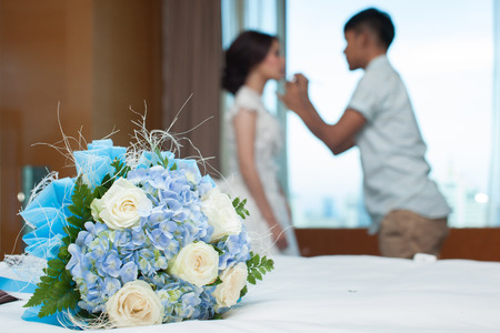 bouquet on bed with background of blurry bride having her make up for her wedding photo