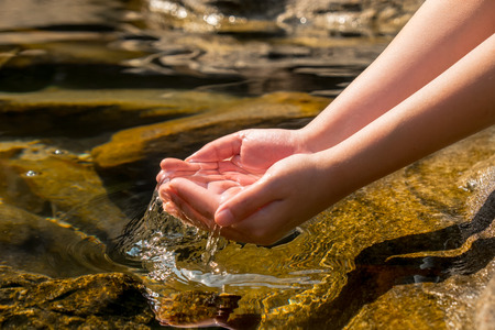 hands holding clear water from natural well