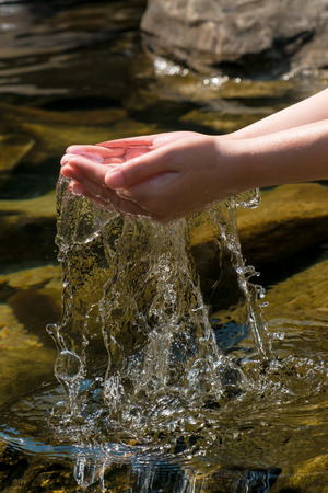 hand lifting up with splash of water in natural stone pool Stock Photo