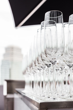 wine glasses prepared for wedding party with the view of another hotel background photo