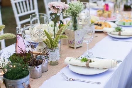 Cena catering al aire libre en la boda con los aderezos caseros de la decoración