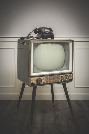 old television: Old Television with 4 legs in the corner of vintage room and a black old telephone on it Stock Photo