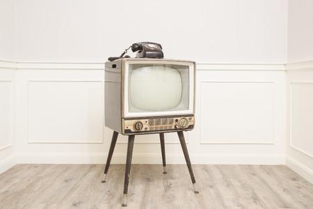 Oude televisie met 4 poten in de hoek van de uitstekende ruimte en een zwarte oude telefoon op het