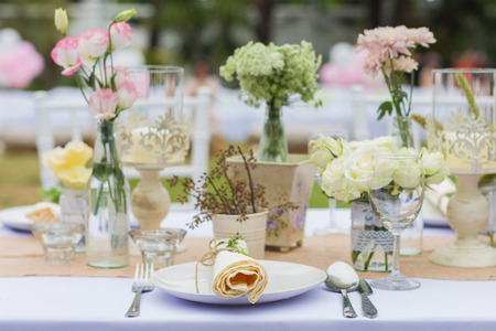 plate setting: Outdoor catering dinner at the wedding with homemade garnishes decoration Stock Photo