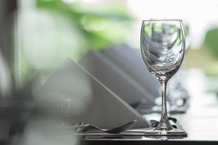 Gießen von Wasser in Glas mit Utensil auf Mittagstisch Standard-Bild