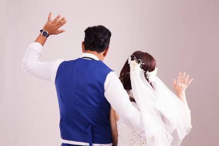 Asian couple waving goodbye pose. Studio photography