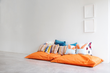Bean bags and pillows in minimalist styled white room