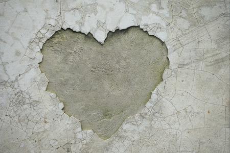 Grieta en forma de corazón en la pared que revela la textura interior del cemento